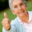 Old woman with thumbs up - Stockfoto
