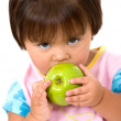 Unhappy girl eating a green apple — Stock Photo