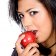 African girl biting an apple — Stock Photo