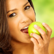 Stock Photo: Beautiful girl eating an apple