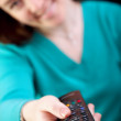 Stock Photo: Girl with television remote control