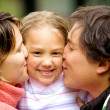 Stock Photo: Parents kissing daughter