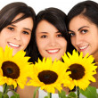 Beautiful female friends holding sunflowers — Stock Photo