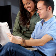 Couple reading a newspaper - Stock Photo