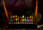 Happy birthday candles on cake — Stock Photo