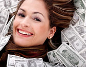 Woman swimming in money — Stock Photo