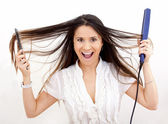 Woman with hair straightener — Stock Photo