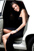 Girl coming out a limousine — Stock Photo