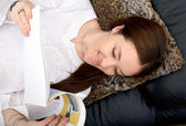 Casual girl reading a holiday brochure — Stock Photo