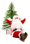 Santa claus against a xmas tree — Stock Photo