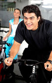 Man cycling at the gym — Stock Photo