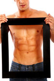 Strong man framing his abs — Stockfoto