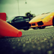 Supercars in the background, cone in the foreground - Stock Photo