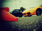 Supercars in the background, cone in the foreground — Stock Photo