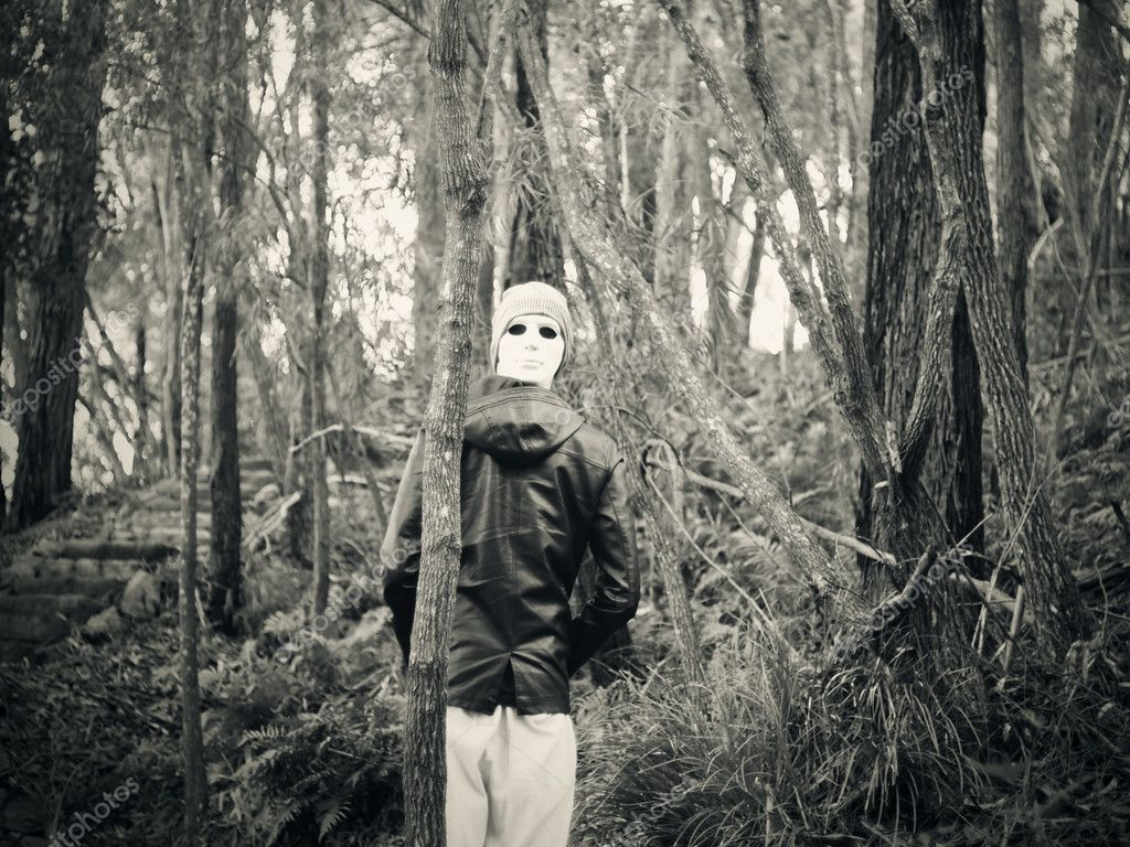 Man wearing white mask standing in the woods  Stock Photo #7594312