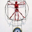 Red toy skeleton, which hangs over a mechanical alarm clock - a — Stock Photo