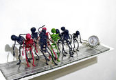 Colorful toy skeletons being dragged behind a clock. — Stock Photo