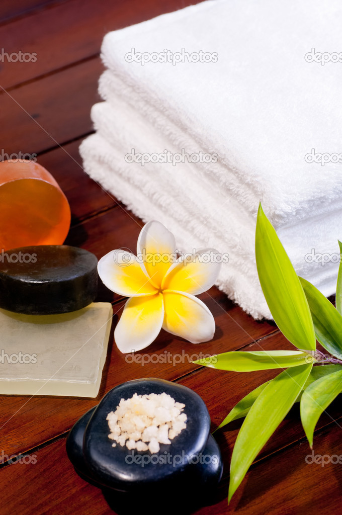 Spa concept with zen stone, bath salt, soap and a yellow frangipani flower on wooden background — Stock Photo #7576591