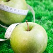 Stock Photo: Two apples on grass with tape measure