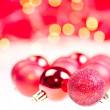 Red Christmas baubles over white and red background — Stock Photo