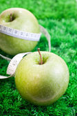 Two apples on grass with tape measure — Stock Photo