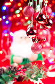 Red Christmas hanging baubles with santa at the background — Stock Photo