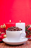 Christmas coffee beans in a cup on a table over red background — Stock Photo
