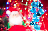 Blue Christmas hanging baubles with santa at the background — Stock Photo