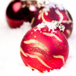 Three Christmas red baubles on snow - Stock Photo