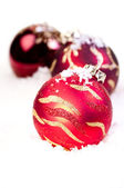 Three Christmas red baubles on snow — Stok fotoğraf
