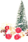 Mini Christmas tree with red and gold baubles on snow — Stock Photo