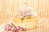 Pink rose tea in a glass teapot — Stock Photo