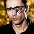 Closeup portraiture of young hard handsome male model with painted face — Stock Photo #7621001