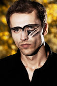 Closeup portraiture of young hard handsome male model with painted face — Stock Photo