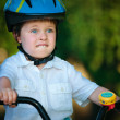 Foto Stock: Terrified boy wearing helmet on bike