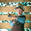 Portrait of a cute boy in hat  playing with a pistol - Stock Photo