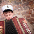 Portrait of a cute boy playing on accordion — Stock Photo