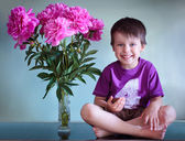 Portrait of a cute boy with peonies bouquet — Stock Photo