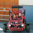 Brother and sister sitting in buggy — Stock Photo
