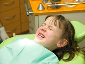 Girl stressed by dental examination — Stock Photo