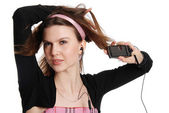 The girl with a cellular telephone listens to music in ear-phone — Stock Photo