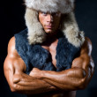 Strong athletic man in a fur cap — Stock Photo