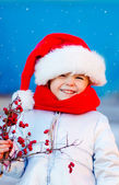 Happy girl in santa hat with red berries — Stock Photo