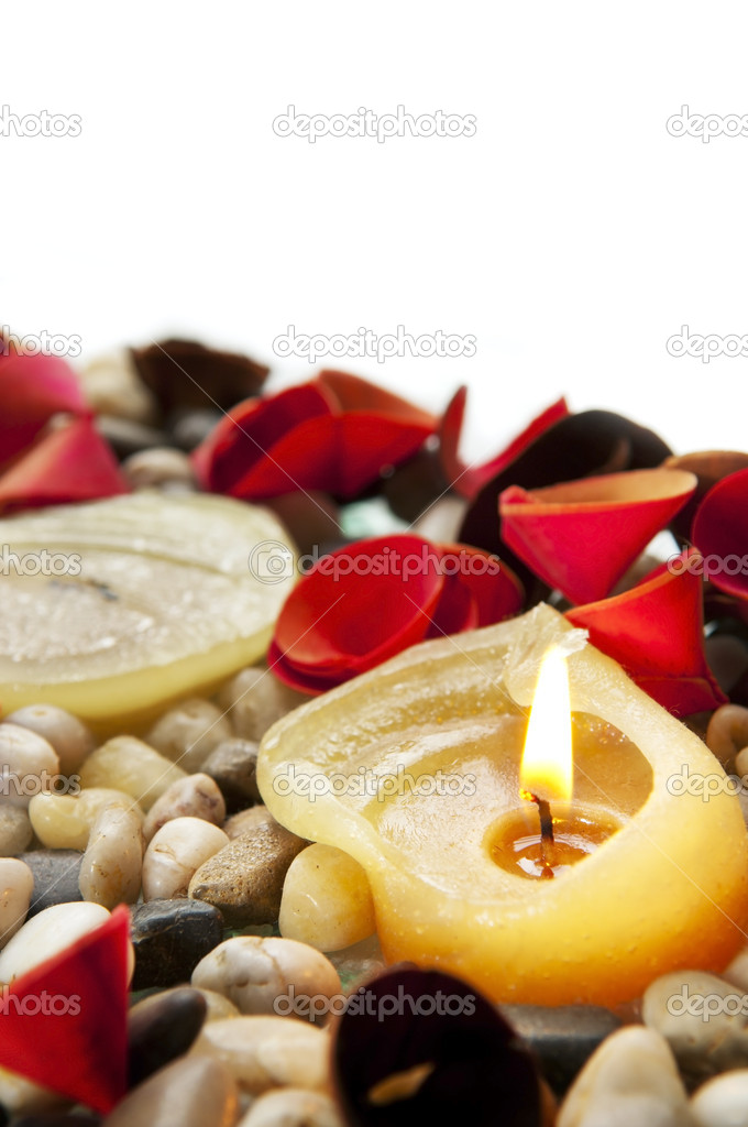 A burning candle amongst small stones and bright petals — Stock Photo #7693201