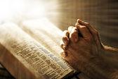 Mans mãos rezando na bíblia — Foto Stock