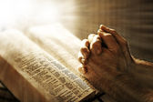 Mans hands praying on Bible — Stock Photo