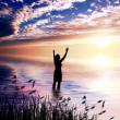 Woman Praising at dawn - Stock Photo