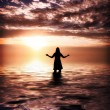Woman Praising at sunrise - Stock Photo