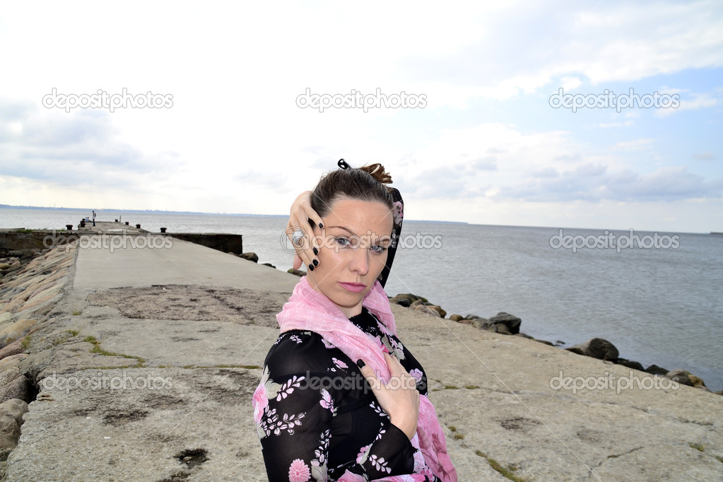 Portrait of a young woman in a rosy scarf on a sea pier — Stock Photo #7803546