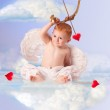 Cute angel baby with bow and arrow, sitting on a cloud — Stock Photo